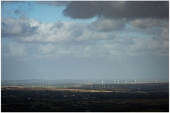 Distant wind turbines as seen from Carn Marth lit by a break in the cloud.  Love or loathe them they are a prominent feature on the landscape.