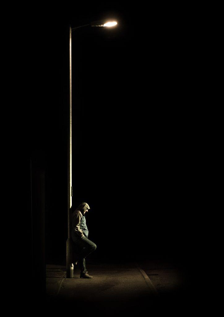 Man under street light at night
